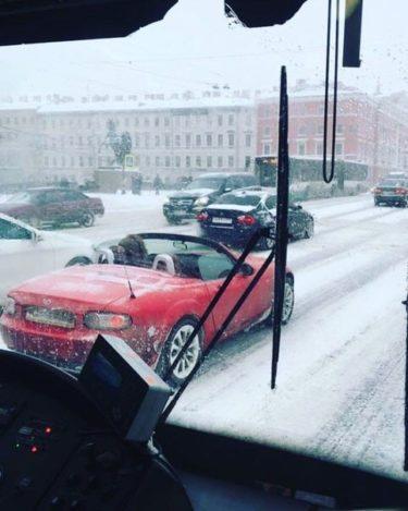 雪の降りしきるロシアで屋根を開けて走るオープンカーがとても寒そう